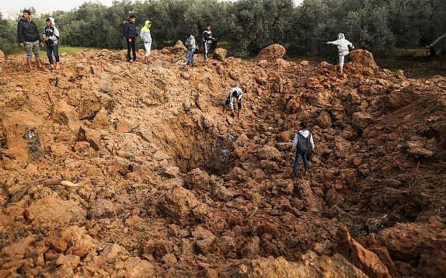 Les Palestiniens inspectent le site d'une frappe aérienne israélienne à Gaza le 18 février 2018 (Crédit : AFP / MAHMUD HAMS)
