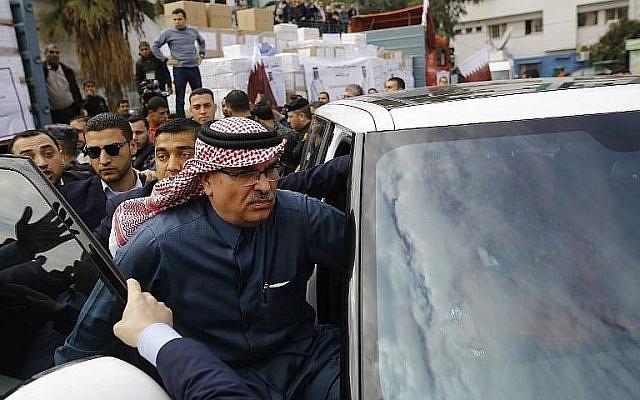 L'envoyé qatari Mohammed Al-Emadi, au centre, quitte une conférence de presse à l'hôpital  Dar al-Shifa de Gaz. Les travailleurs hospitaliers ont tenté de l'approcher alors qu'il partait mais ont été repoussés par les policiers du Hamas, le 19 février 2018 (Crédit : AFP Photo/Mohammed Abed)