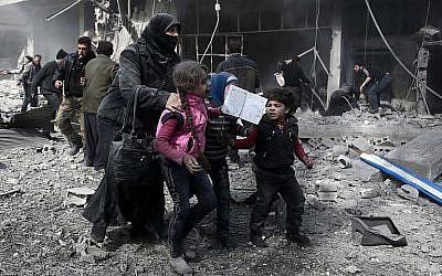 Une femme syrienne et des enfants courent pour trouver un abri   après un bombardement gouvernemental dans la ville d' Hammuriyeh, détenue par les rebelles,  à la Ghouta orientale, détenue par les rebelles, aux abords de Damas, le 19 février 2018 (Crédit :  AFP PHOTO /Abdulmonan Eassa)