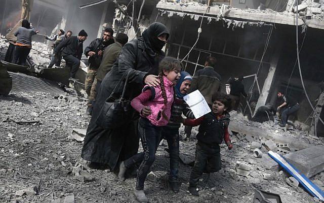 Une femme et des enfants syriens courent se réfugier parmi les décombres de bâtiments après l'attentat à la bombe perpétré par le gouvernement dans la ville rebelle de Hamouria, dans la région assiégée de Ghouta Est, à la périphérie de la capitale Damas, le 19 février 2018. (AFP/Abdulmonam Eassa)