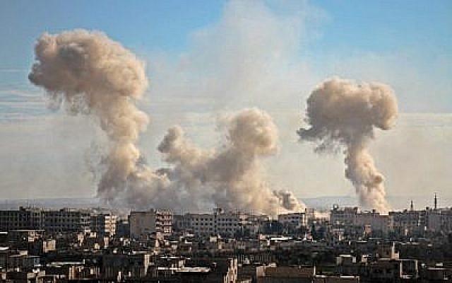 La fumée s'élève des bâtiments après le bombardement du village de Mesraba, dans la région assiégée de Ghouta Est, dans la banlieue de la capitale Damas, le 19 février 2018. (AFP PHOTO / Hamza Al-Ajweh)