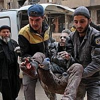 Des volontaires de la Protection civile, connus sous le nom de Casques blancs, transportent un blessé dans un hôpital de fortune dans la ville de Douma, contrôlée par les forces du régime dans la région assiégée de la Ghouta orientale, en périphérie de Damas, le 20 février. 2018 (Crédit : Hamza Al-Ajweh / AFP)