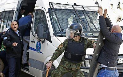 La police palestinienne empêche des manifestants d'approcher un véhicule transportant des membres du conseil municipal de New York et des groupes de la société civile alors qu'ils quittent un immeuble après avoir visité une ONG dans la ville de Ramallah, en Cisjordanie, le 22 février 2018 (Crédit : Abbas Momani/AFP)