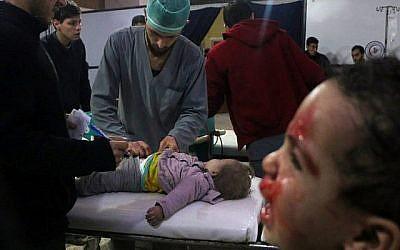 Les médecins syriens s'occupent d'un bébé, alors qu'un enfant pleure à côté d'eux dans une clinique de fortune après les bombardements du gouvernement syrien à Douma, dans la région assiégée de Ghouta Est, à la périphérie de la capitale Damas, le 22 février 2018. (AFP/Hamza Al-Ajweh)