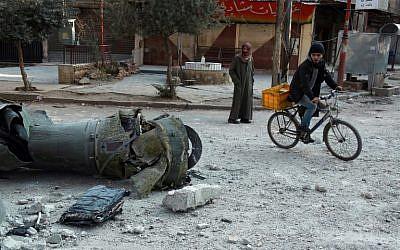 Des hommes passent devant les restes d'une roquette dans la ville de Douma, dans la région assiégée de la Ghouta aux abords de la capitale de Damas, suite aux frappes aériennes menées par les forces du régime, le 23 février 2018 (Crédit :  AFP PHOTO / HAMZA AL-AJWEH)