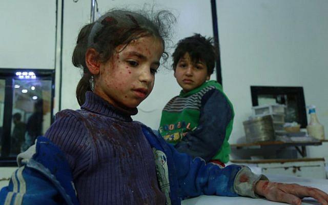 Deux enfants blessés attendent une aide médicale   dans la ville de Douma, dans la région assiégée de la Ghouta  aux abords de la capitale de Damas, suite aux frappes aériennes menées par les forces du régime, le 23 février 2018 (Crédit :  AFP PHOTO / HAMZA AL-AJWEH)