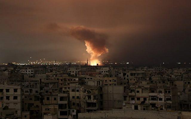 De la fumée s'élève suite à une frappe aérienne du régime sur la région assiégée de la Ghouta orientale aux abords de la capitale de Damas, dans la nuit du 23 février 2018 (Crédit : AFP/ Ammar SULEIMAN)
