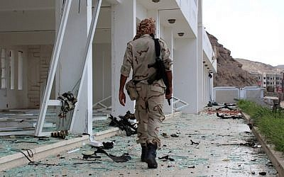 Un combattant du conseil de transition du sud séparatiste marche sur le site de deux attentats-suicides à la voiture piégée qui ont ciblé le siège d'une unité terroriste le jour précédent, dans le port d'Aden, dans le sud du Yémen, le 25 février 2018 (Crédit : AFP PHOTO / SALEH AL-OBEIDI)