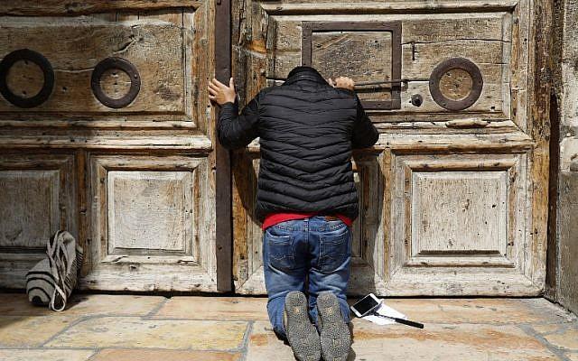 Un pèlerin prie devant la porte fermée de l'église du saint-sépulcre dans la Vieille Ville de Jérusalem, le 25 févcrier 2018 (Crédit :AFP PHOTO / GALI TIBBON)
