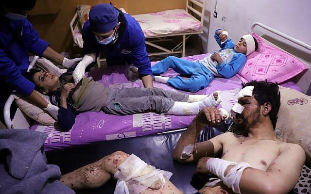Les médecins soignent Omar, âgé de dix ans, qui a été blessé lors d'une frappe aérienne qui a tué plusieurs membres de sa famille dans leur maison d'Otaybah, dans l'enclave syrienne de Ghouta Est tenue par les rebelles, alors que son père et sa sœur de sept ans, Manar, le surveillent dans un hôpital de fortune le 25 février 2018. (AFP PHOTO / AMER ALMOHIBANY)