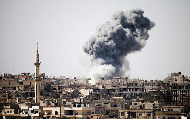 Photo d'illustration : De la fumée apparait au loin après les frappes aériennes signalées sur la ville de Daraa, dans le sud de la Syrie, le 22 février 2017 (Mohamad Abazeed / AFP)