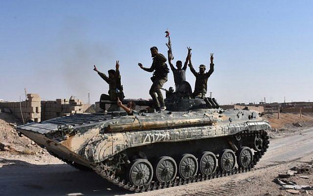 Les forces gouvernementales syriennes se réjouissent dans la ville de Deir Ezzor, dans l'est de la Syrie, le 11 septembre 2017, alors qu'elles continuent d'avancer avec la couverture aérienne russe dans l'offensive contre le groupe terroriste islamique. (AFP Photo/George Ourfalian)