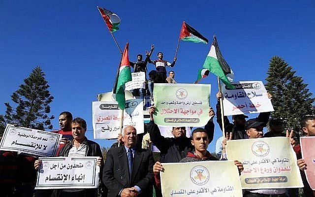 Des Palestiniens brandissent le drapeau national durant une manifestation à Gaza, le 3 décembre 2017, en soutien aux pourparlers de réconciliation entre le Hamas et le Fatah (Crédit : AFP/Mohammed Abed)