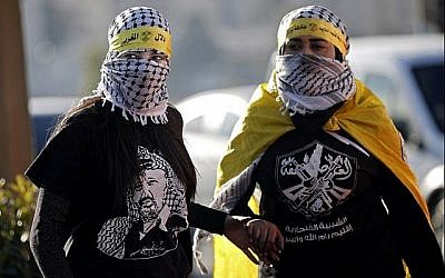 Des manifestantes palestiniennes masquées portant des chemises et des drapeaux du parti Fatah du Président de l'AP, Mahmoud Abbas, lors d'une manifestation à Ramallah, en Cisjordanie, le 11 décembre 2017. (AFP Photo/Thomas Coex)