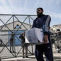 Les réfugiés palestiniens récoltent des colis humanitaires dans un centre de distribution des Nations unies à Rafah, dans le sud de la bande de Gaza, le 21 janvier 2018 (Crédit : AFP/ SAID KHATIB)
