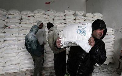 Les Palestiniens récupèrent de l'aide alimentaire dans un centre de distribution alimentaire des Nations Unies à Khan Yunis, dans le sud de la bande de Gaza, le 28 janvier 2018. (Dit Khatib/AFP)