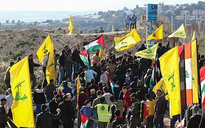 Les soldats israéliens (en haut à gauche) et les Casques bleus (en haut à droite) regardent les partisans libanais du mouvement chiite Hezbollah assister à un rassemblement contre la décision du président américain de reconnaître Jérusalem comme capitale d'Israël, le 28 janvier 2018, dans le village dans le sud du Liban d'Alma al-Shaab, à la frontière avec Israël (Crédit : AFP PHOTO / Mahmoud ZAYYAT)
