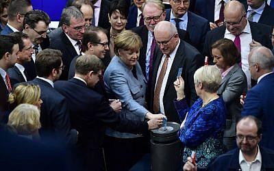 La chancelière allemande et leader du parti de l'Union chrétienne-démocrate (CDU), Angela Merkel (au centre), vote à la chambre basse allemande du Bundestag à Berlin le 1er février 2018 lors du vote du l'adoption d'une loi restreignant le regroupement familial des réfugiés en Allemagne (Crédit : PHOTO AFP / Tobias SCHWARZ