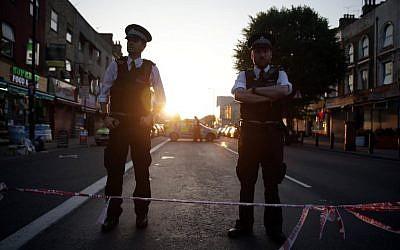 Des policiers montent la garde après une attaque dans le quartier de Finsbury Park, contre une mosquée, à Londres, le 19 juin 2017. (Crédit : Daniel LEAL-OLIVAS / AFP)