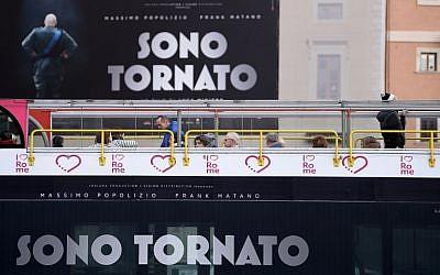 """Un bus de tourisme passe devant une affiche du film italien  """"Sono Tornato"""" (Je suis de retour) dans le centre de Rome, le 2 février 2018 (AFP PHOTO / FILIPPO MONTEFORTE"""