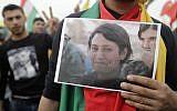 Une libanaise de la communauté kurde brandit une photo de Barin Kobani, 23 ans, membre des Unités de protection de la femme (YPJ), torturée et tuée par rebelles alliés aux forces turques. Photo prise durant une manifestation contre l'offensive turque à Afrine, devant l'ambassade américaine à Aaoukar, au nord de Beyrouth, le 5 février 2018. (Crédit : AFP / Joseph EID)