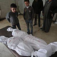 Des enfants devant des cadavres emballés, après des frappes du régime dans la Ghouta orientale, en périphérie de Damas, le 5 février  2018. (Crédit : AFP / ABDULMONAM EASSA)
