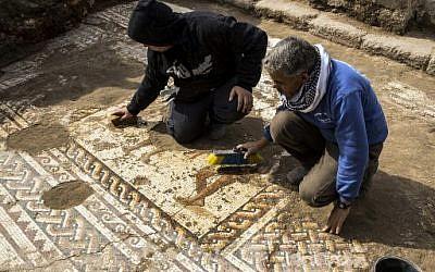 Des ouvriers de l'Autorité israélienne des Antiquités nettoient une mosaïque romaine rare du 2e ou 3e siècle au Parc National de Césarée, en Israël, le 8 février 2018 (AFP PHOTO / JACK GUEZ)