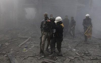 Un homme blessé reçoit de l'aide pour sortir des décombres après une frappe aérienne dans l'enclave rebelle d'Arbin, dans la Ghouta orientale, près de Damas, le 8 février 2018. (Crédit : AFP/ ABDULMONAM EASSA)