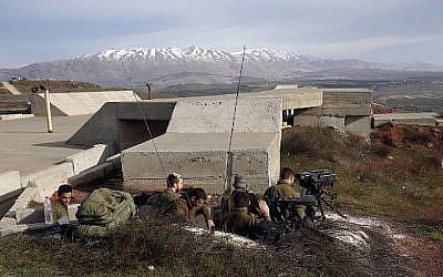 Une photo prise le 10 février 2018 montre des soldats israéliens prenant position dans le plateau du Golan près de la frontière syrienne. (Crédit : AFP / JALAA MAREY)