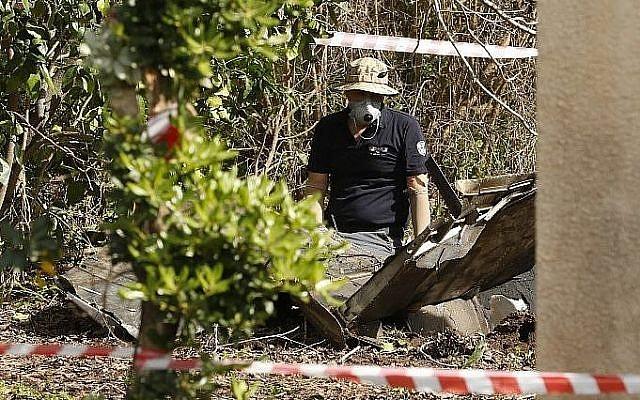 Une photo prise dans la vallée du Jezreel dans le nord d'Israël montre des spécialistes en explosifs en train d'inspecter des débris, le 10 février 2018 (Crédit : AFP PHOTO / Jack GUEZ)
