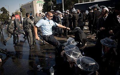 Des manifestants ultra-orthodoxes se heurtent à la police lors d'une manifestation contre l'arrestation d'un homme ayant refusé de faire son service militaire, près du bureau de recrutement de l'armée à Jérusalem, le 17 septembre 2017 (Crédit : Yonatan Sindel / Flash90)