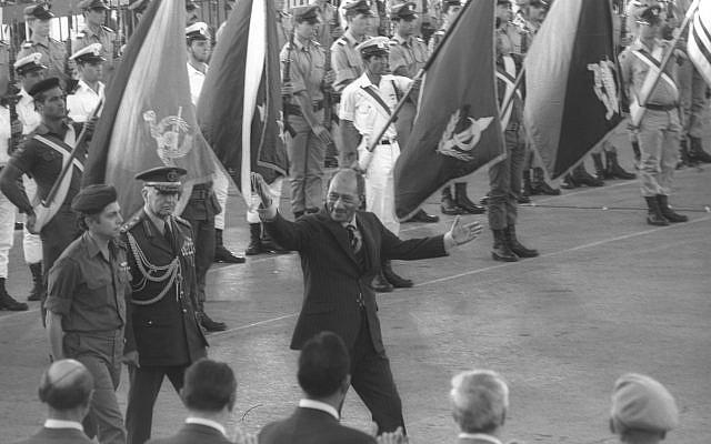 Le président égyptien Anouar el-Sadate salue les Israéliens avant de quitter l'aéroport Ben Gourion, le 21 novembre 1977 (archives Miki Tzarfati / GPO)