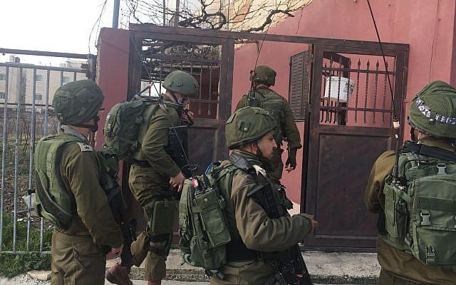 Les soldats israéliens marchent dans la ville palestinienne de Halhul, au nord de Hébron, après qu'un habitant a poignardé un gardien de la sécurité lors d'un attentat terroriste dans une implantation voisine, le 7 février 2018 (Crédit : Armée israélienne)