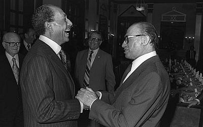 Le Premier ministre israélien Menachem Begin (à droite) et le président égyptien Anouar el-Sadate rient ensemble à l'hôtel King David, le 19 novembre 1977 (Crédit : archives Ya'akov Sa'ar / GPO)