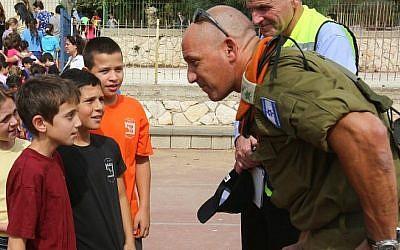 Un officier du Front intérieur parle avec des élèves pendant un exercice d'urgence dans une école israélienne au mois d'octobre 2012 (Crédit : Oren Nahshon/Flash90)