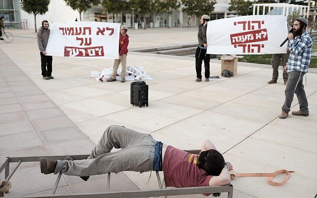 Des militants de droite assistent à une manifestation à Tel Aviv, mettant en scène des tortures présumées par le Shin Bet contre des présumés terroristes juifs (Crédit : Tomer Neuberg/Flash90)