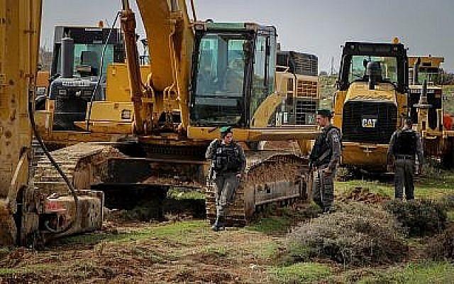Des agents de la police des frontières surveillent près des tracteurs pendant les préparatifs pour l'évacuation et la démolition de l'avant-poste illégal de Netiv Haavot le 7 février 2018. (Gershon Elinson/Flash90)