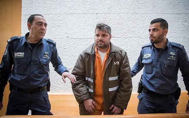 Yosef Haim Ben-David, l'un des juifs suspectés du meurtre de Muhammed Abu Khdeir, sous escorte policière au tribunal de district de Jérusalem, pour son appel, le 8 février 2018.  (Crédit : Yonatan Sinde/Flash90)