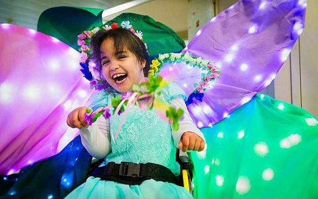 Yarden, une fée heureuse dans son fauteuil roulant décoré en fleur, à Beit Issie Shapiro (Autorisation : Beit Issie Shapiro)
