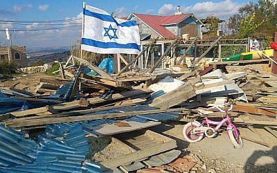Un drapeau israélien flotte sur les ruines d'une maison en bois dans l'avant-poste de Netiv Ha'avot après sa démolition par les forces de sécurité israéliennes le 29 novembre 2017. (Crédit : autorisation Campagne pour sauver Netiv Haavot)