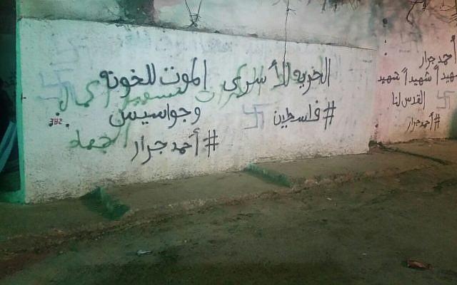 Des croix gammées et d'autres graffitis sur le mur extérieur de ce que certains juifs considèrent comme le site funéraire du personnage biblique Yehoshua Bin Nun dans le village palestinien de Kifl Haris, en Cisjordanie, le 22 février 2016 (Crédit : Sécurité Samarie )
