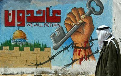 Un Palestinien marche devant une fresque murale appelant au retour des réfugiés palestiniens (Crédit :  Abed Rahim Khatib/Flash90)