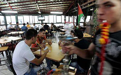 Des jeunes palestiniens fument des narguilés et jouent aux cartes au café Sultan à Ramallah, en Cisjordanie, le 11 septembre 2011 (Crédit : Nati Shohat / Flash90)