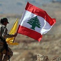 Un membre du groupe terroriste du Hezbollah tient des drapeaux libanais et du Hezbollah lors d'un voyage de presse près de la ville frontalière d'Arsal, le 25 juillet 2017 (Photo AFP / Stringer)
