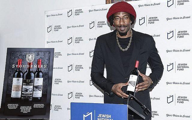 Amar'e Stoudemire montrant l'un des vins de sa collection de vins casher israéliens, à New York, le 20 février 2018. (Crédit : Autorisation Jewish National Fund-USA via JTA)