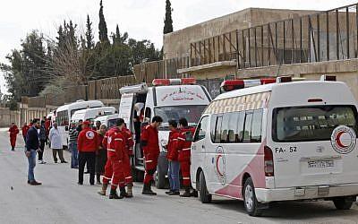 Les ambulanciers du Croissant-Rouge syrien attendent à côté des ambulances prêtes à transporter les blessés au point de contrôle de Wafideen, en périphérie de Damas, le 28 février 2018, au cours d'une opération qui permettrait à quelque 400 000 personnes vivant dans la zone tenue par les rebelles de quitter l'enclave assiégée grâce à des couloirs sécurisés (Crédit : PHOTO AFP / LOUAI BESHARA)