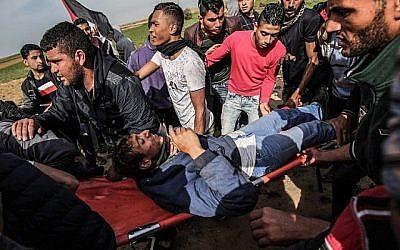 Des Palestiniens aident à évacuer un manifestant blessé sur une civière lors d'affrontements avec les troupes israéliennes près de Khan Yunis, près de la frontière entre Israël et la bande de Gaza, le 2 mars 2018. (AFP PHOTO / DIT KHATIB)