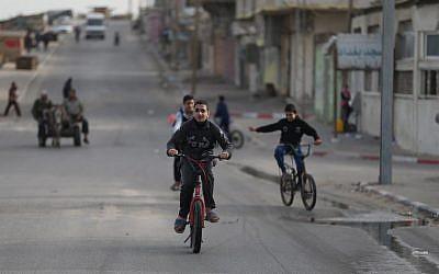Des garçons palestiniens font du vélo dans la ville de Gaza le 8 mars 2018 (Crédit : AFP / MOHAMMED ABED)