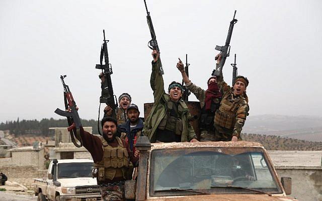 Des rebelles syriens soutenus par la Turquie font signe en descendant une route dans la région de Hallubi, au nord d'Afrin, le 8 mars 2018. (AFP PHOTO / Nazeer al-Khatib)