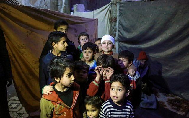 Les enfants syriens posent pour une photo dans un abri antiaérien artisanal dans la ville de Douma, détenue par les rebelles, dans la Ghouta orientale, située dans les faubourgs de  Damas, le 8 mars 2018 (Crédit : AFP PHOTO / HAMZA AL-AJWEH